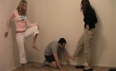 Two chicks are taking turns giving a crazy dude kicks to th
