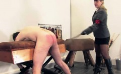 Uniformed femdom spanks subs ass with wet twigs