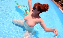 Mature redhead Red XXX masturbating in the pool